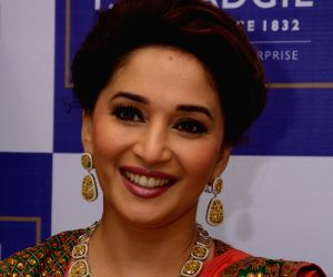 Bollywood actress Madhuri Dixit Nene inaugurating new showroom of PN Gadgil Jewelers along with the owners Daji Kaka and Saurabh Gadgil in Mumbai on August 3, 2013.
