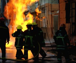 Firefighters try to douse a fire in a building near the Avellaneda bridge
