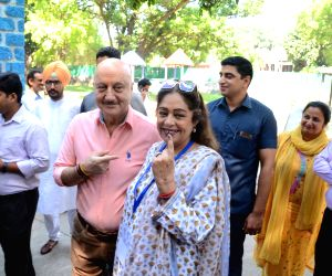 Chandigarh: Actors Kirron Kher and Anupam Kher show their his forefinger marked with indelible ink after casting vote during the seventh and the last phase of 2019 Lok Sabha Elections at a polling booth in Chandigarh on May 19, 2019. Kirron is sittin