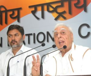 Congress leader Kapil Sibal (R) addresses a press conference in New Delhi on March 30, 2018