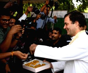 Congress President Rahul Gandhi distributes sweet on his birthday as he arrives to attend the Congress Working Committee (CWC) meeting at the party's headquarters, in New Delhi, on June ...
