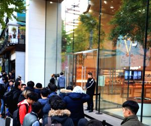 Customers stand in line outside the Apple store in Seoul on Nov. 2, 2018, to buy the new iPhone, which officially went on sale locally on the day. The gadgets are priced from 990,000 won ...