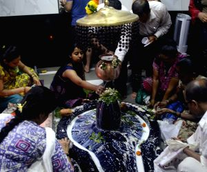 Devotees throng a Shiva temple during Sawan