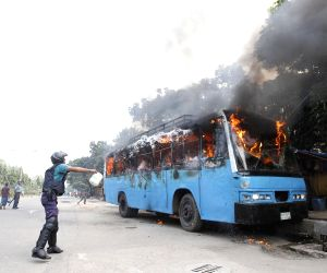 A policemen throws water to a burning bus before a strike in Dhaka