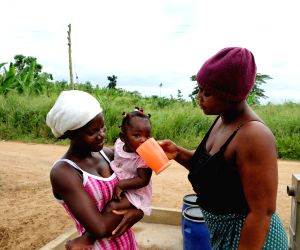 EASTERN REGION (GHANA), June 20, 2018 A woman gives water to a baby near a borehole in Agyakwa Village, Eastern Region, Ghana, on June 18, 2018. The government of China is providing 1,000 ...
