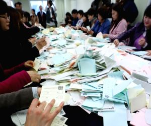 Employees demonstrate how to sort ballots at an office of the National Election Commission in Incheon, west of Seoul, on March 29, 2018. South Korea is gearing up for the June 13 local ...