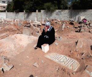 Palestinian's prays over his relative's grave