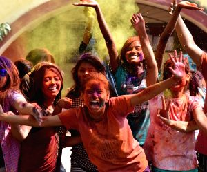 Girls play with colors on the eve of Holi in Guwahati on Mar 1, 2018.