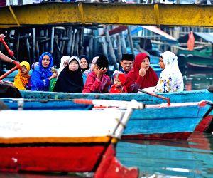 Muslims who live near a traditional port in Sunda Kelapa arrive by boat to attend the Eid Al-Fitr celebration
