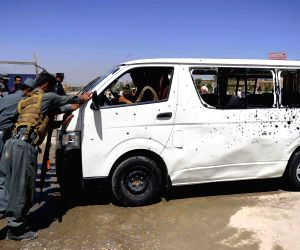 An Afghan man washes a damaged bus at the blast site in Kabul, Afghanistan