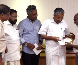 Kochi Biennale Foundation president, Bose Krishnamachari hands over an amount of Rs 3-crore  to Kerala CM Pinarayi Vijayan towards the Chief Minister's Distress Relief Fund for the 2018 flood victims, at the CMO, Thiruvananthapuram on July 10. From l