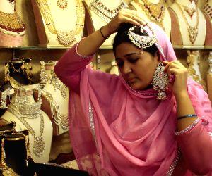 A Pakistani woman buys jewelry at a shop ahead of the Eid al-Fitr