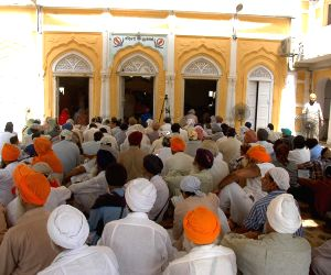 Indian Sikh devotees pray at the Gurdwara Dhara Sahib in Lahore