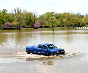 A pickup truck runs on a flooded street in Laurel