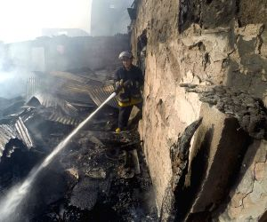 Manila (Philippines): A firefighter puts out a fire that hit a slum