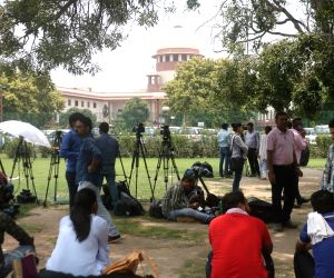 Media persons wait during SC hearing on Section 377