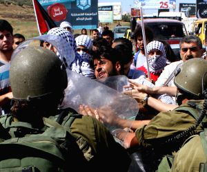 Palestinian protesters clash with Israeli soldiers during a protest against the ongoing Israeli air campaign