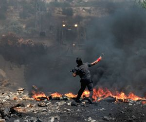 A Palestinian protester throws stones at Israeli soldiers during a protest
