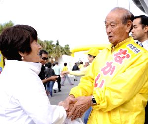 Naha (Japan): Hirokazu Nakaima shakes hands with a woman to appeal for the upcoming election