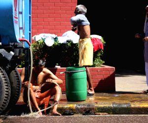 A man bathes on footpaths of Delhi
