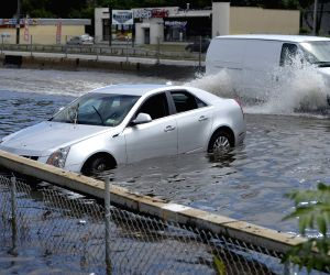 New York: A car drives on a waterlogged road following heavy rains and flash flooding