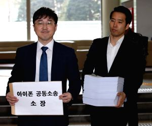 Officials of Hannuri Law, a local law firm, arrive at the Seoul Central District Court on March 30, 2018, to file a lawsuit against Apple Inc. and its South Korean unit for intentionally ...
