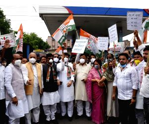Bihar Congress president Madan Mohan Jha with party's supporters and workers protest against frequent hikes in the prices of petrol and diesel, and demand roll back of prices, in front of a fuel station in Patna