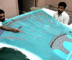 A Pakistani worker works on a handmade suit