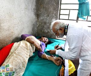 "Prime Minister Narendra Modi signs an autograph for a woman who among others, got injured when the portion of a tent collapsed during ""Kisan Kalyan"" rally, in West Bengal's Midnapore ..."