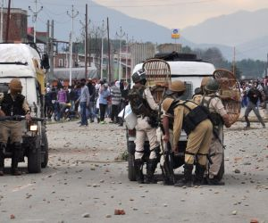 Protesters pelt stones on security personnel on Srinagar-Baramulla highway in Srinagar on June 22, 2018.