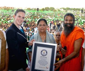 Rajasthan Chief Minister Vasundhara Raje being presented with the Guinness Book of World Record certificate during the Fourth International Yoga Day celebrations, in Kota on June 21, 2018. Also ...