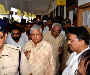 : Ranchi: Former Bihar Chief Minister and RJD chief Lalu Prasad being taken away by police after he surrendered in a special Central Bureau of Investigation (CBI) court to serve his sentence in a ...