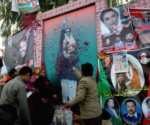 Supporters of the Pakistan Peoples Party (PPP) shower rose petal on the poster of former premier Benazir Bhutto at the site of her assassination in Rawalpindi, ..