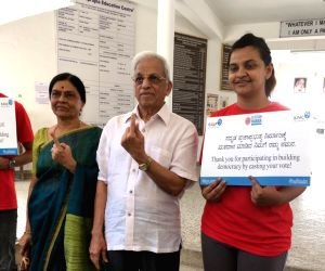 Retired Supreme Court Judge Justice Shivaraj V Patil accompanied by his family members, shows his inked finger after casting his vote for the second phase of 2019 Lok Sabha elections, in ...