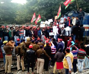 Samajwadi Party (SP) workers staging a demonstration against CBI raids at the residence of a party leader, block railway tracks disrupting railway services in Uttar Pradesh's Chandausi on ...