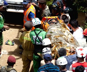 Rescuers carry a survivor to an ambulance after a collapse in an artisanal gold mine in San Juan Arriba
