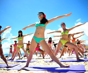 People practice yoga during a massive bikini party