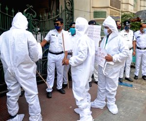 Social workers wearing protective suits and masks display placards near the Election Commission office during a demonstration for the ongoing state legislative election and campaign rallies amidst the rising number of Covid-19 coronavirus cases in Kolkata