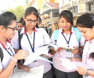 Students busy in last minute revision as they wait outside their exam center to appear for their  class 12th Board examinations in Bengaluru on Mar 1, 2018.