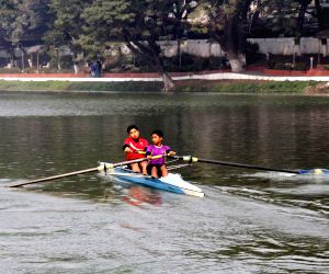 Students take part in a rowing competition at Dighalipukhuri
