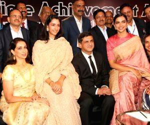 Veteran badminton player Prakash Padukone with his family including actress Deepika Padukone and shuttler PV Sindhu pose for a photograph after receiving the Lifetime Achievement Award ...