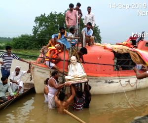 Free Photo: People of flood-affected village rescue Mahatma Gandhi's statue