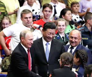 """VLADIVOSTOK, Sept. 12, 2018 - Chinese President Xi Jinping and Russian President Vladimir Putin talk with children at the All-Russian Children's Center """"Ocean"""" while attending commemoration ..."""