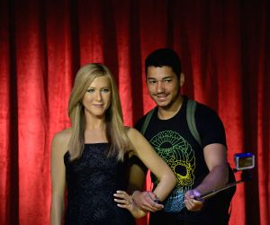 Visitors poses with the wax figure of actress Jennifer Aniston at the Madame Tussauds