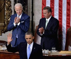 U.S. President Barack Obama waves after delivering the State of the Union Address to a joint session of Congress as Vice President Joe Biden  and U.S. House Speaker John Boehner applaud on Capitol Hill