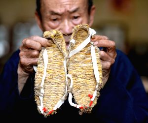 Straw sandal craftsman Chen Luoshou shows a pair of straw sandals